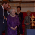 Prince Harry and Queen Elizabeth view the Rugby World Cup trophy during a reception at Buckingham Palace; 12-10-2015