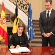 Queen Letizia signs the condolence book at the Belgian Embassy in Madrid as King Felipe watches on